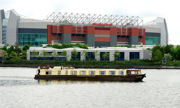 LS Lowrey barge at Salford Quays passing Old Trafford Manchester United FC Football Ground